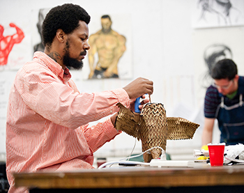 An undergraduate student works on a three-dimensional mixed-media drawing in class, Art tile