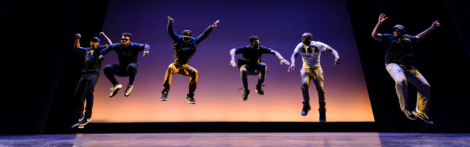 Six student dancers jump mid-air during a dance performance